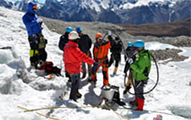 Participants learning ice drilling technique to maintain stakes on glacier
