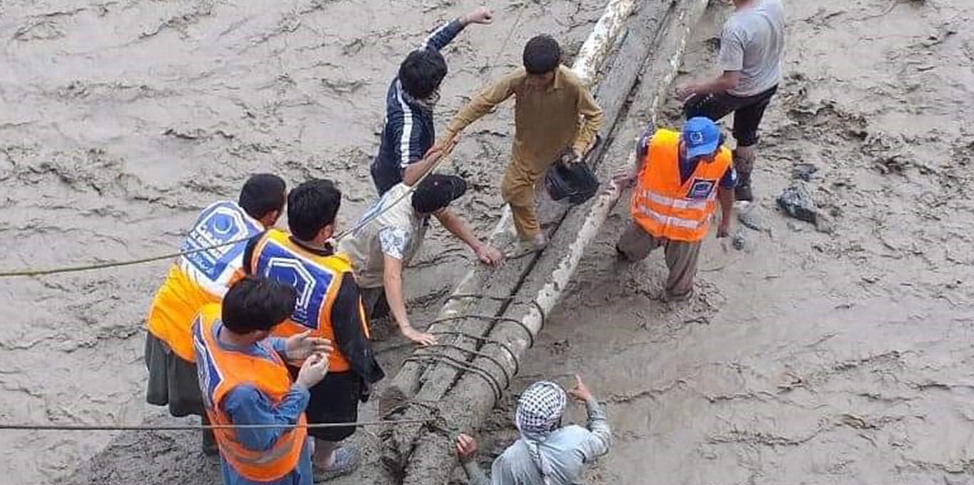 Reshun village locals and volunteers build a makeshift bridge